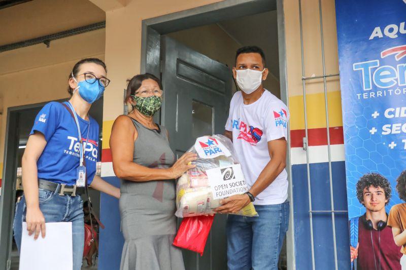 Em Belém, moradora recebe cesta de alimentos das mãos da equipe do Projeto ParáPaz Solidário nesta terça-feira (4)