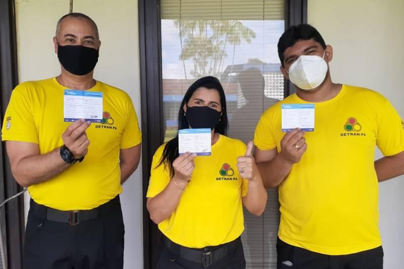 Agentes do Detran mostram aliviados a carteira de vacinação contra a Covid-19