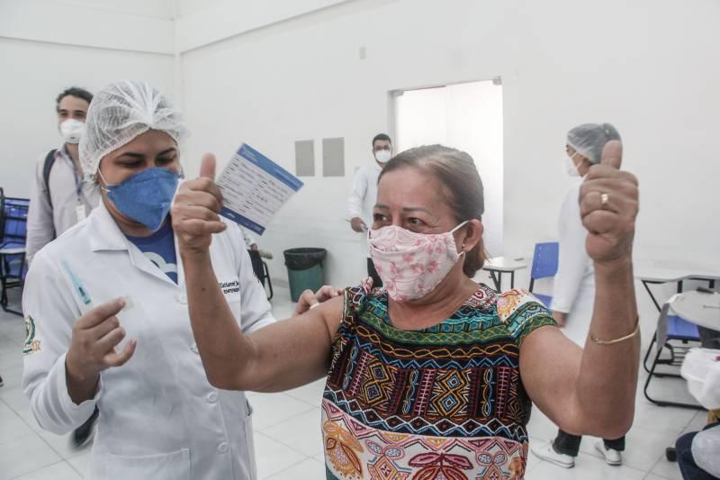 A aposentada, Maria do Carmo, toma a 2ª dose do imunizante no campus CCBS da Uepa e vibra de alegria, nesta quarta-feira (16)