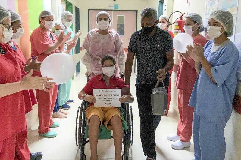 Na saída, ao lado do pai, o menino foi aplaudido pelos profissionais que cuidaram dele durante 17 dias
