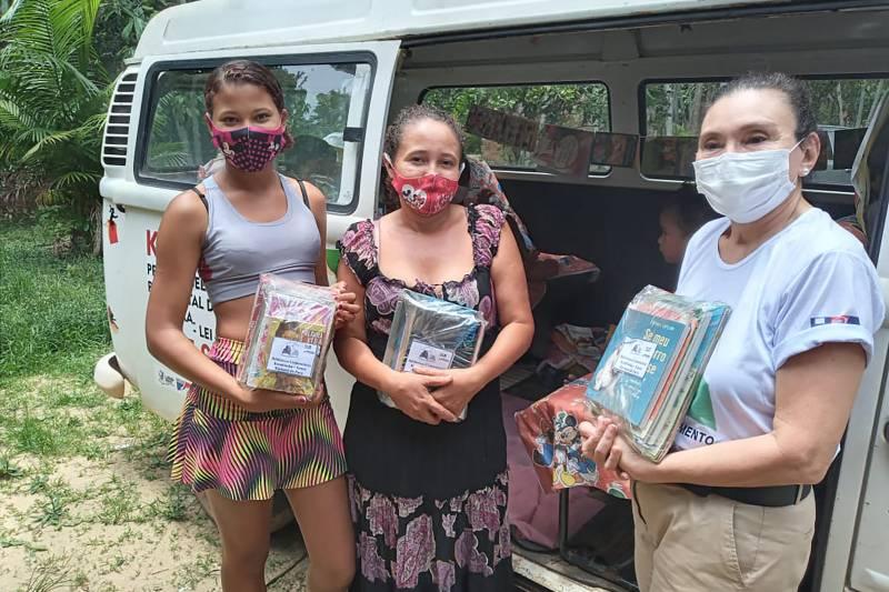 A coordenadora do Portal, Sandra Batista (d) durante a entrega dos livros ao Projeto Kombiteca